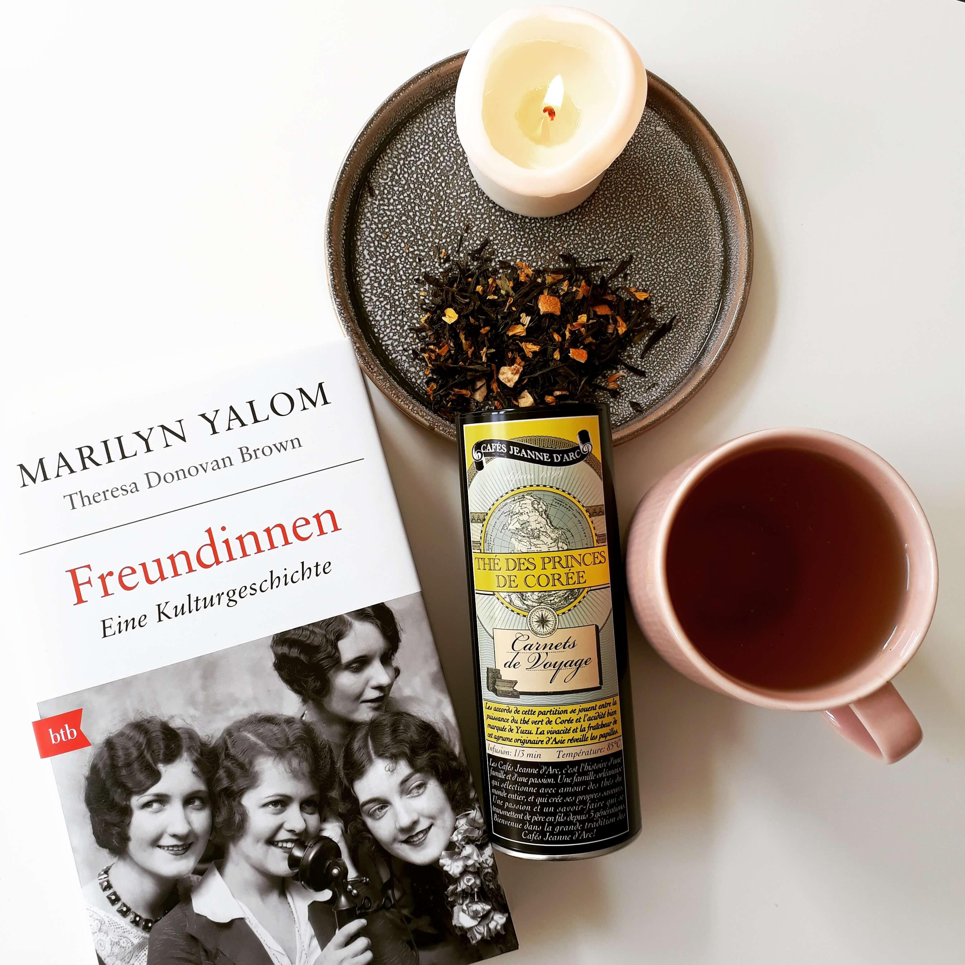 Buch mit Kerze und Teetasse