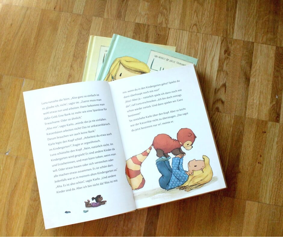 Aufgeklapptes Buch, man sieht Luna mit dem Katzenbären spielen