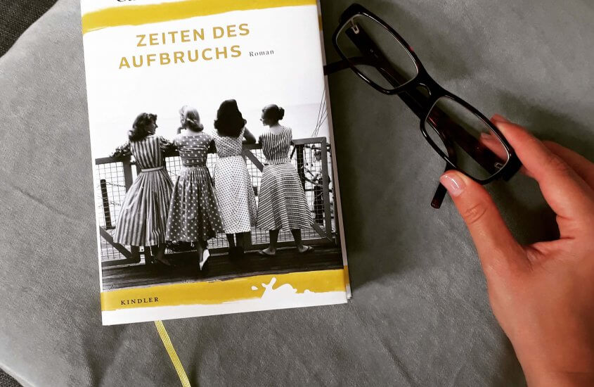 Buch auf Kissen neben Brille