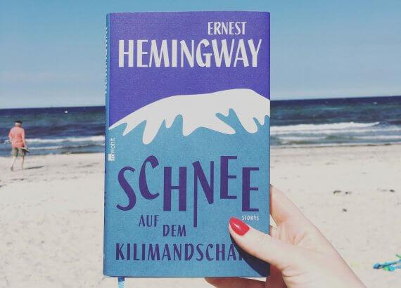 Das Buch Schnee auf dem Kilimandscharo am Strand hochgehalten