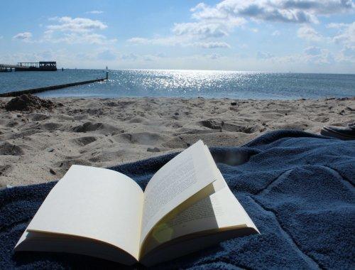 Aufgeschlagenes Buch am Ostseestrand bei Sonnenschein