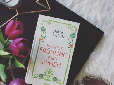 """Das Buch """"Wenn es Frühling wird in Wien"""" neben einem Strauß lila Tulpen auf einem Holztisch"""