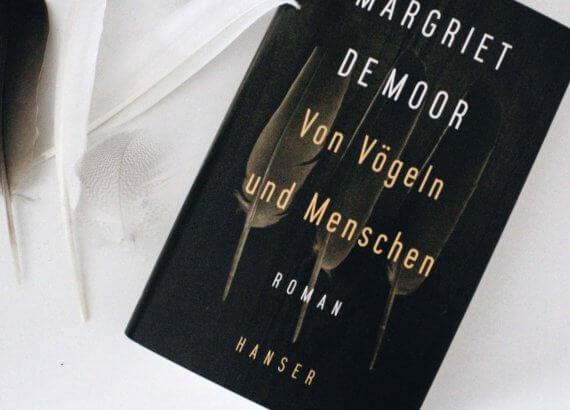 """Dunkles Cover con """"Von Vögeln und Menschen"""" mit Federn darauf neben echten Federn."""