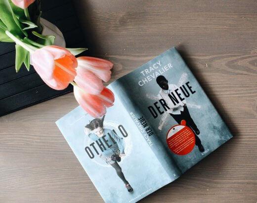 """Aufgeklapptes Buch """"Tracy Chevalier Der Neue"""" unter rosa Tulpen"""