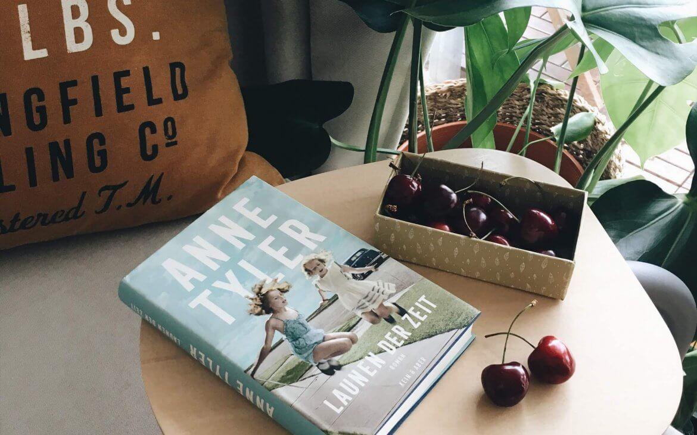 Roman Anne Tyler Launen der Zeit neben einer Schale Kirschen auf einem Sofatischchen
