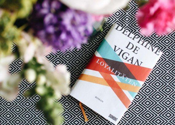 Das bunt-gestreifte Cover von Loyalitäten unter einem bunten Blumenstrauß
