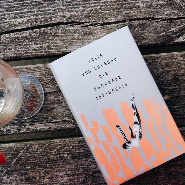 Das Buch Die Hochhausspringerin neben einem Glas Wein