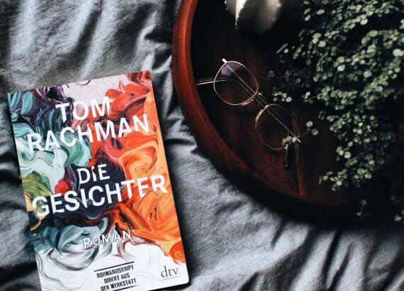"""Der Roman """"Die Gesichter"""" auf grauer Decke neben Tablet mit Pflanze"""