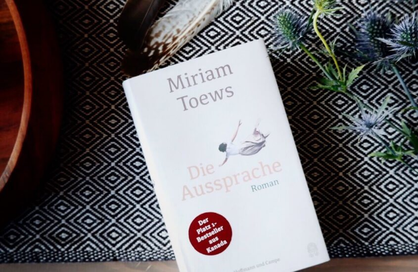 Roman Die Aussprache von Miriam Toews neben Federn und Disteln auf Tisch