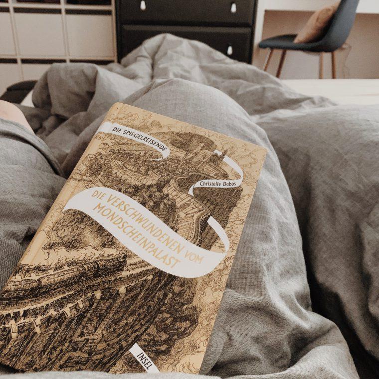 """Das Buch """"Die Verschwundenen vom Mondscheinpalast"""" auf Bettdecke"""